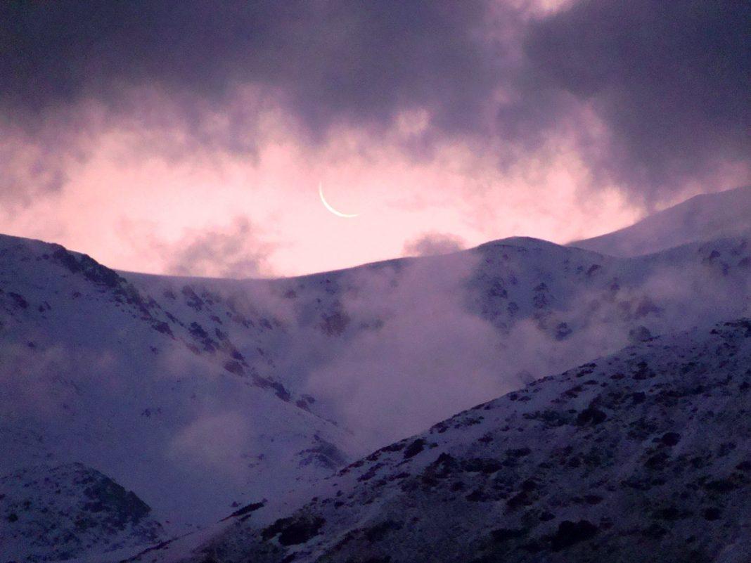 La luna apenas sugerida en una delgada curva blanca parece esconderse tras las nubes y las cumbres del mágico Cordón del Plata. (Foto: Ana Vogel)
